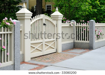 White gate and fence with pink roses on house entrance. Elegance, craftsmanship, home improvement.
