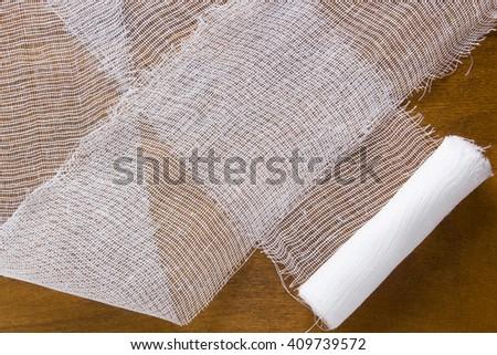 White gauze bandage on a wooden background - stock photo