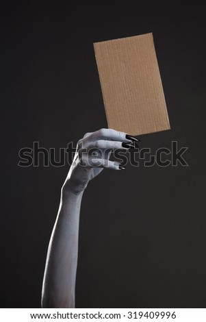 White ghost or witch hand with black nails holding blank cardboard, Halloween theme  - stock photo