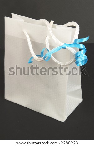 White gift bag with blue ribbon isolated on black - stock photo