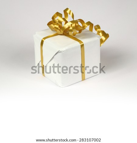 White gift box with golden ribbon bow - stock photo