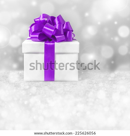 White gift box with purple ribbon bow, - stock photo