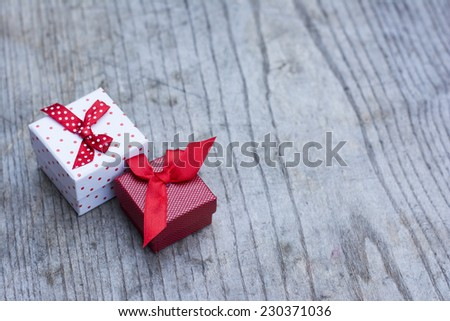 White gift box with red dots with smaller red gift box placed on wooden background  - stock photo