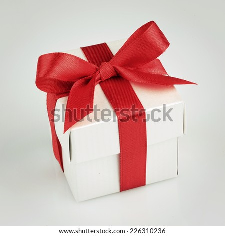 white gift box with red ribbon and bow top view
