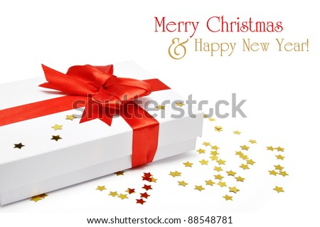 White gift box with red ribbon and golden confetti over white background - stock photo
