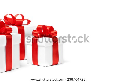 White gift box with red ribbon bow and christmas balls around, isolated on white background - stock photo