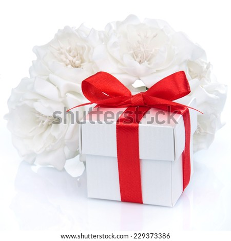 white gift box with red ribbon, bow and flowers on a white background - stock photo