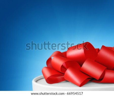 White gift box with red ribbon on blue background with copy space - stock photo