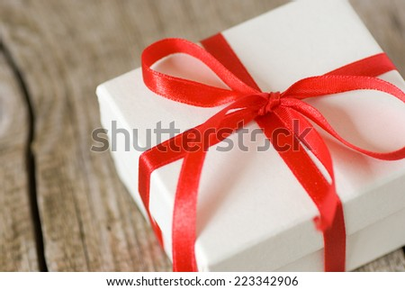 White gift box with red ribbon on old wooden table