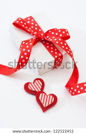 White gift box with red ribbon on red background - stock photo