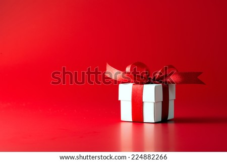 White gift box with ribbon on red background - stock photo