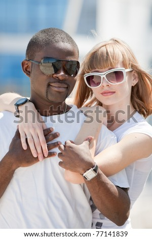 White girl and black guy outdoors. Young man and woman in sunglasses are looking at camera - stock photo