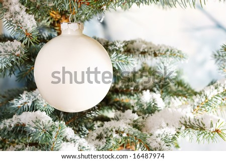 White glass Christmas bauble on a snow encrusted tree - stock photo