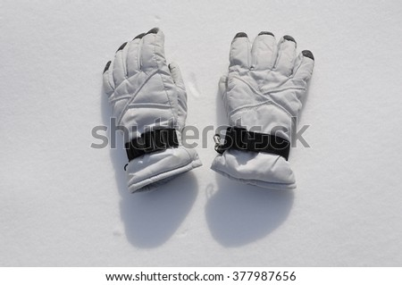 White gloves in snow  - stock photo