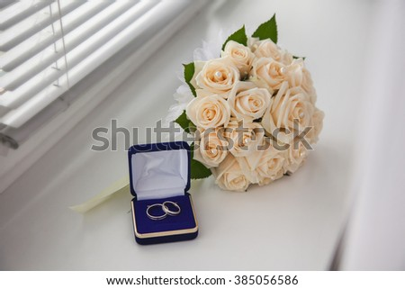 white gold, wedding bands, wedding rings from white gold in the blue box, wedding jewelry, wedding preparation, a bouquet of white roses, white light background - stock photo