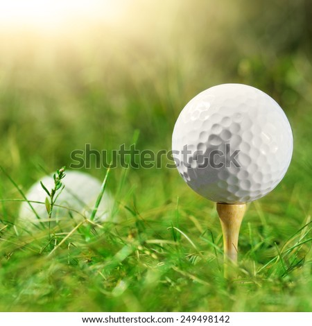 White golf ball being set on bamboo tee - stock photo