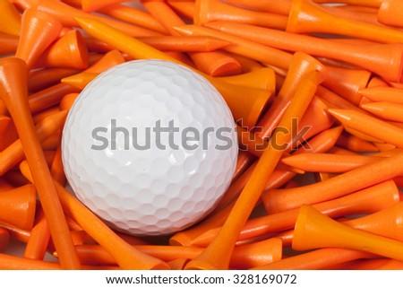 White golf ball lying between orange wooden golf tees - stock photo