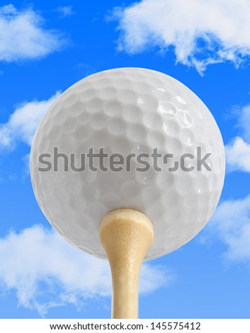 White Golf Ball on a Tee with a blue sky background - stock photo