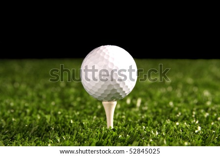 White golf ball on a white tee in green grass(artificial turf) with black background - stock photo