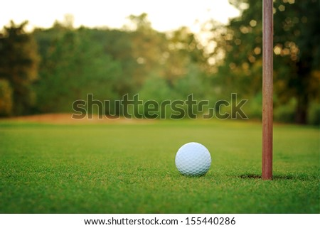 White golf ball on putting green with bunker in background - stock photo