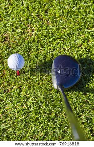 white golf ball on red tee in grass with driver close up ,ready to be hit, shot from above - stock photo