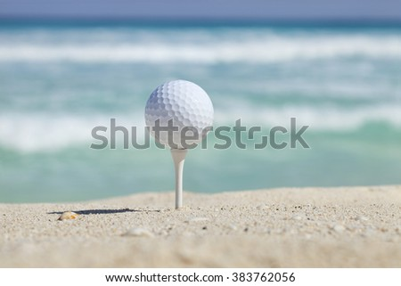 White golf ball on tee in sand of beach with soft focus ocean waves behind - stock photo