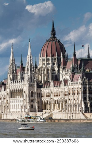 White Gothic building of the Hungarian Parliament in Budapest. The building is located on the Danube River on blue sky background - stock photo