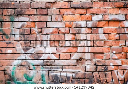 White graffiti detail on old brick wall. - stock photo