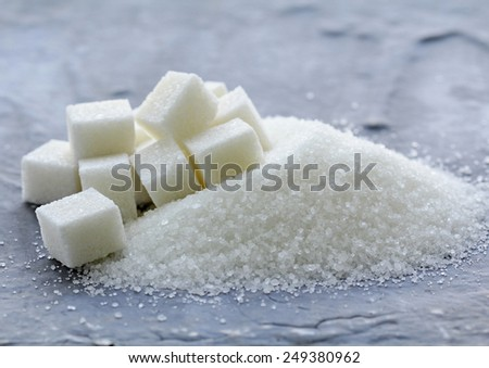 white granulated sugar and refined sugar on a gray background - stock photo