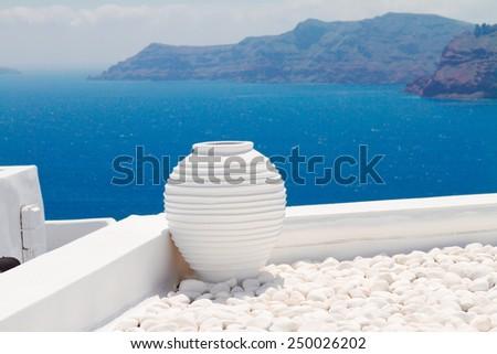 white greek amfora against volcano caldera and sea, beautiful details of Santorini island, Greece - stock photo