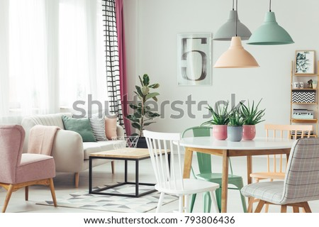 White, grey and green chair at round table under pastel lamps in modern flat interior with sofa and pink armchair