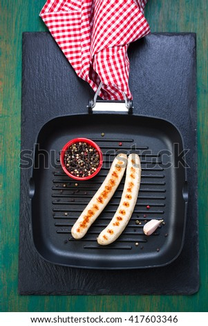 White grilled sausages with black pepper in a grill pan with red napkin on an old vintage green wooden background, top view - stock photo