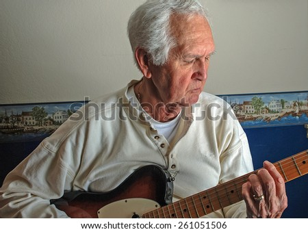 White-haired older caucasian male playing guitar for his own pleasure in casual surrounding of his own home. - stock photo
