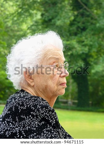 White-haired woman in profile with green trees in background - stock photo