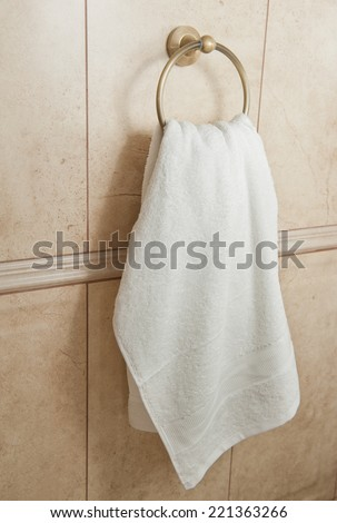 white hand towel on metallic hanger. Close up background of a bathroom hand towel on tile wall. - stock photo