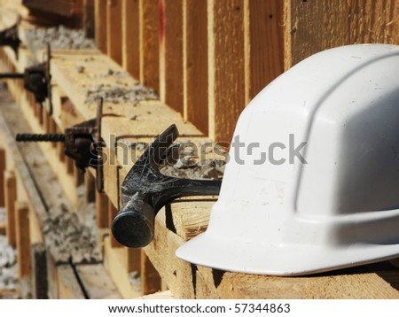 White hard hat and hammer on the wooden construction frame - stock photo