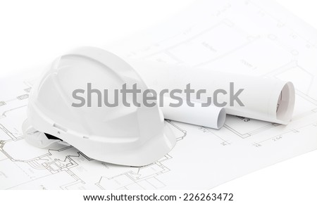 White hard hat near working drawings on white background - stock photo