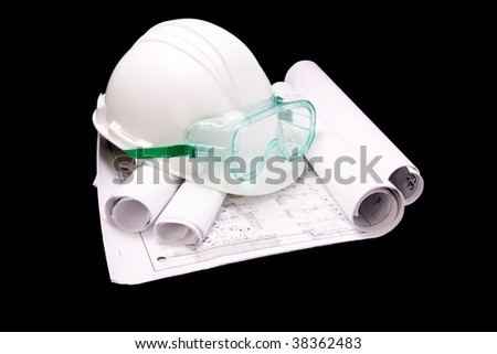 White hard hat with safety goggles on partially unrolled blueprints.  Isolated on black. - stock photo