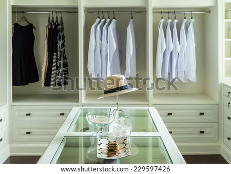 white hat and jewelry set on a dresser table in a walk in closet room. - stock photo