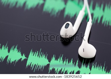 white headphones on top of computer tablet. - stock photo