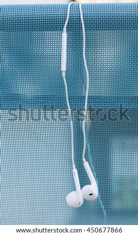 White headset over blue deckchair, vertical image - stock photo