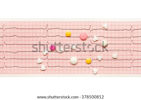 White heart shape tablets and white, yellow and pink tablets on paper ECG results isolated on white background. Clipping path included. - stock photo