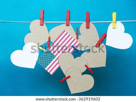 White hearts - room for text, USA flag hanging on colorful pegs, clothespin  on a line. United States of America holidays info. Martin Luther King Day, National Freedom Day, Abraham Lincoln day.