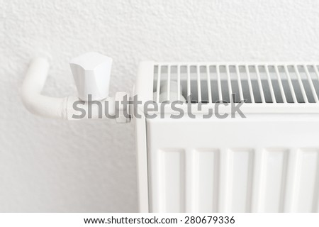 White heating radiator in an apartment. Detail shot with copy space - stock photo