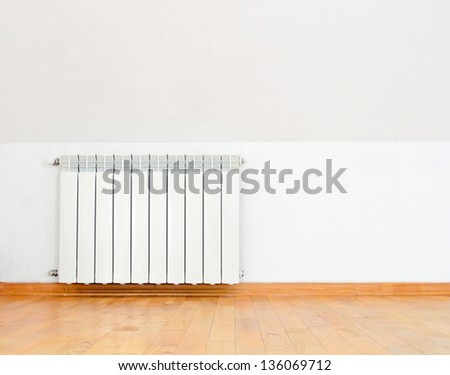white heating radiator on wall and wooden floor - stock photo