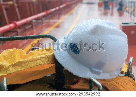 white helmet and gloves lying on the ship's bitts in the rain - stock photo