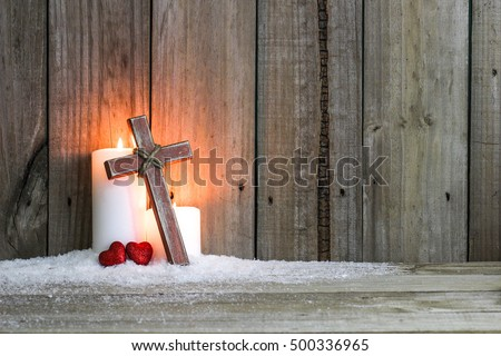 White Holiday Candles Glowing Behind Wooden Cross With Red Hearts In Snow By Antique Rustic Wood