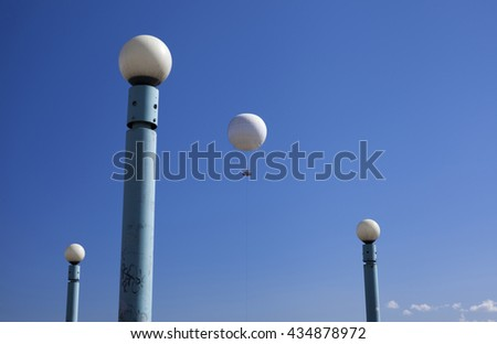 White hot air balloon between white ball street lamps against blue sky.  - stock photo