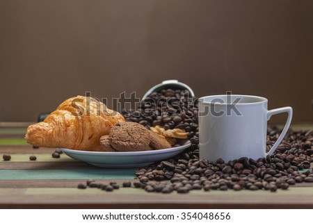 White hot coffee cup with cookies and beans - stock photo
