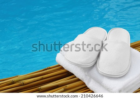 White hotel / home/ spa / wellness slippers with towel on bamboo wood with swimming pool - water - sea background with space for text - summer time - stock photo
